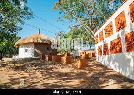 Udaipur, India - December 12, 2017 : Indian folk village Shilpgram, traditional house and sculpture - Stock Photo