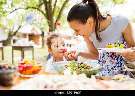 Family celebration outside in the backyard. Big garden party. Birthday party. Young mother with a small girl standing at the table with food. - Stock Photo