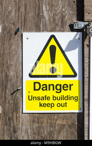 Warning sign saying Danger Unsafe building keep out attached to wooden door - Stock Photo