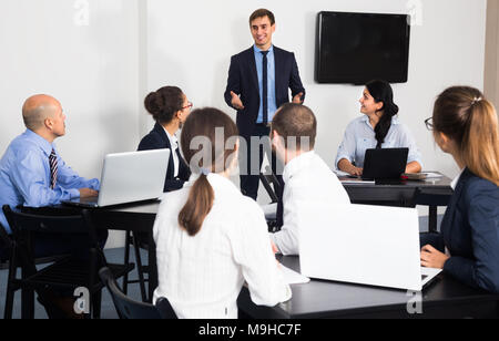 caucasian employee presenting his idea on project to team in office - Stock Photo