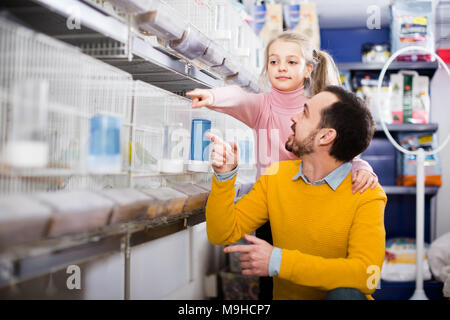 Young dad with his daughter admire different species of birds in a pet shop - Stock Photo