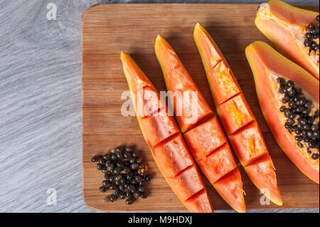 Papaya fruit cut in slices on wooden background