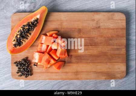 Papaya fruit cut in slices on wooden background - Stock Photo