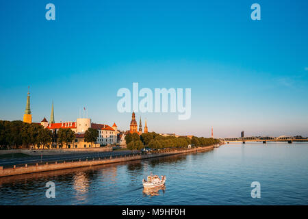 Scenic View To Promenad Of Daugava, In Riga, Latvia. Old Church Towers And Medieval Castle On Background. Seafront Named Ab Dambis. Evening  View With - Stock Photo