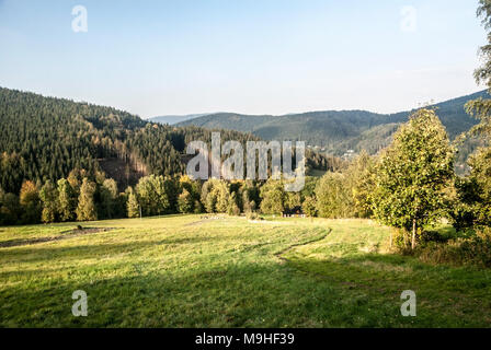 meadow with hiking trail, forest covered hills and blue sky above Krasna village in Moravskoslezske Beskydy mountains in Czech republic during nice au - Stock Photo