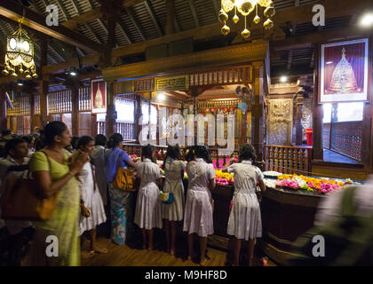School students and teachers praying inside Temple of the Tooth, Kandy, Sri Lanka, Asia. - Stock Photo