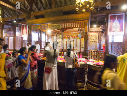 People praying inside Temple of the Tooth, Kandy, Sri Lanka, Asia. - Stock Photo