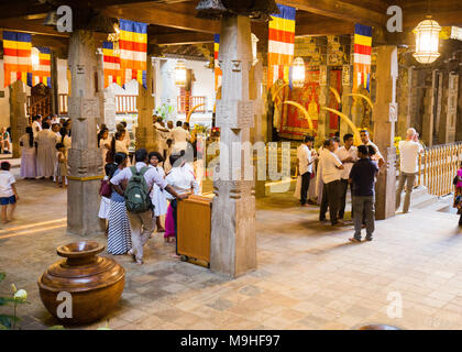 School students and tourists standing inside Temple of the Tooth, Kandy, Sri Lanka, Asia. - Stock Photo