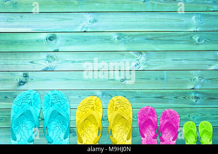 Colorful flip flops of a family of four on a turquoise wood planks background with copy space, family summer beach concept - Stock Photo