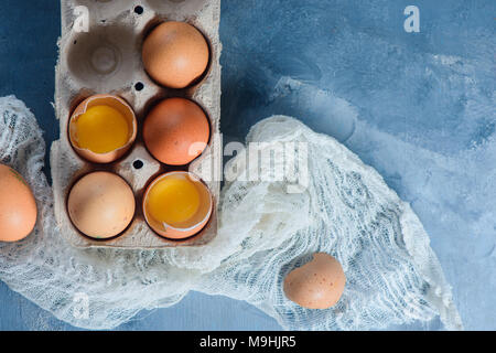 Fresh eggs, whole and broken, in a paper packaging on a concrete background. Fresh ingredients for Easter cooking. Close-up with copy space - Stock Photo