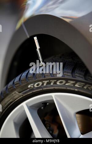 Taking tyre tread depth gauge readings - Stock Photo
