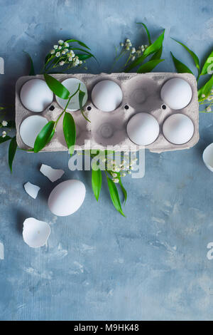 Chicken eggs, whole and broken, in a paper packaging on a concrete background with green leaves and spring flowers. Eco cooking concept with copy space. - Stock Photo