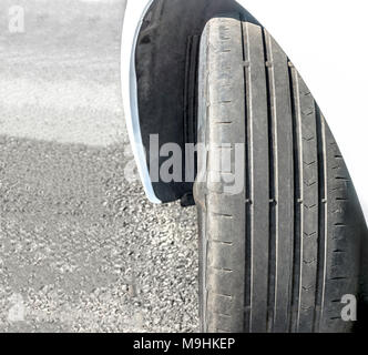 Badly worn out car tire tread and damaged bulb like side due to wear and tear or because of poor tracking or alignment of the wheels, dangerous. - Stock Photo
