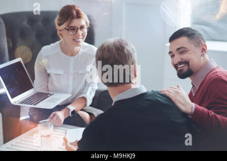 Happy bearded man looking at his colleague - Stock Photo