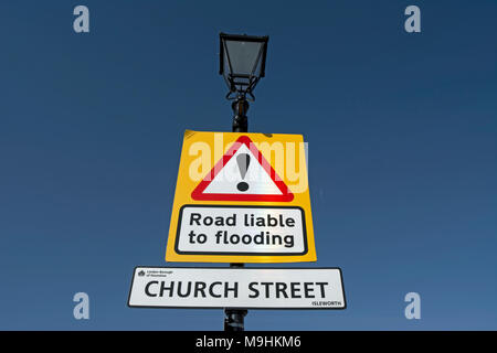 street name sign for church street, isleworth, middlesex, england, below a road liable to flooding warning sign - Stock Photo