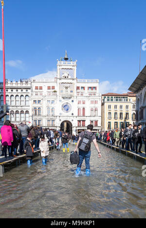 Tourist with luggage wading trough Acqua Alta flooding in Piazza San Marco (St Marks Square), Venice, Italy with lines of people on passerelles - Stock Photo