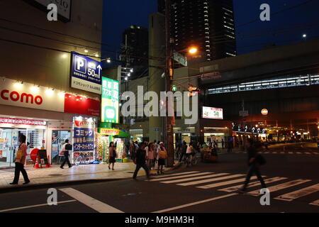 Pedestrians cross the street using the Zebra crossing in Osaka, Japan - Stock Photo