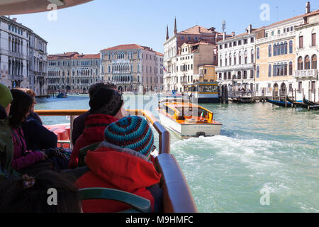 Passengers first person POV on a vaporetto waterbus  travelling down the Grand Canal, Venice, Italy towards Ca' Foscari University with a water taxi p - Stock Photo