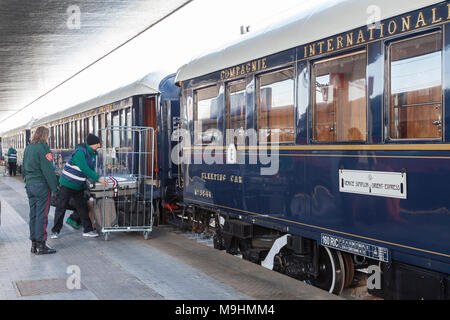 Porter loading suitcases onto the luxury train the Venice Simplon Orient-Express, Venice St Lucia station, Venice, Veneto, Italy watched by a security - Stock Photo