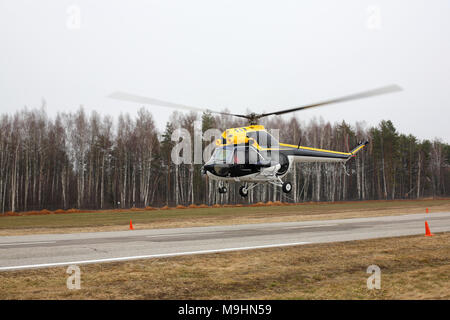 Aircraft - Big black-yellow helicopter side view makes flight at low height on cloudy sky background. - Stock Photo