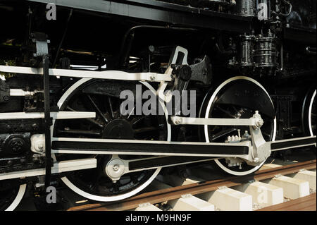 Closeup of the steel wheels of a steam engine. - Stock Photo