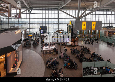 Air travellers waiting in the departures area of Heathrow Airport, Terminal Five. Sitting area, phone charging stations, Caviar House, Chanel, people, - Stock Photo