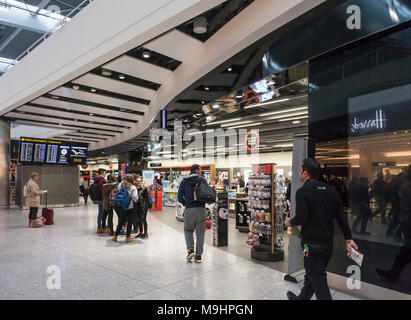 Passengers and staff in and outside the Dixons Travel shop in Heathrow Airport terminal Five. Deaprtures board/Flight information. - Stock Photo