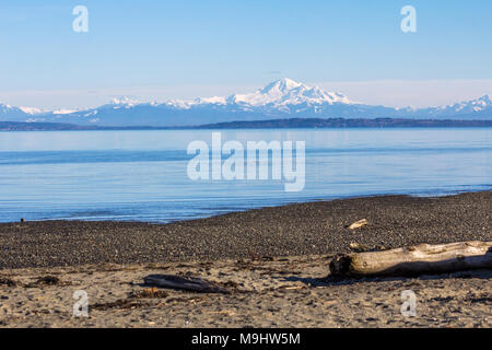Looking east from beach of Boundary Bay Park in Tsawwassen, BC  towards Blaine and Mount Baker in Washington State on a beautiful, sunny, winter day - Stock Photo