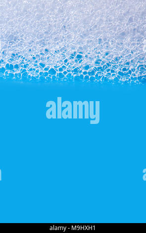 White soap bubbles foam isolated on blue background. Suds shower texture macro view photo, copy space - Stock Photo
