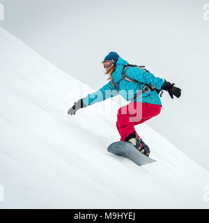 pretty young woman on the snowboard riding in the mountains - Stock Photo