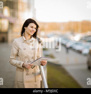 Modern business woman working on a digital tablet, standing next to an office building - Stock Photo