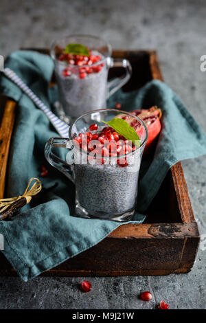 Raw chia pudding with pomegranate seeds in glass jars - Stock Photo