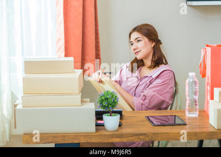 Young happy attractive female asian online seller working at home in her bedroom, thinking about her successful online business - Stock Photo