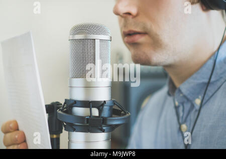 Man recording an advertisement on the radio station. - Stock Photo