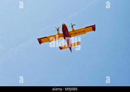 Firefighter airplane in the sky over the Mediterranean Sea near Omis in Croatia - Stock Photo