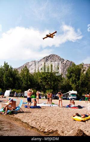 Omis, Croatia. 15 August, 2015: People watching and making photos of firefighters airplane in action. - Stock Photo