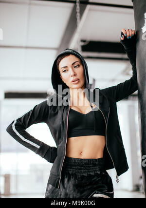 pretty female with perfect fit is snuggling agains boxing bag in boxing club. thinking sportswoman - Stock Photo