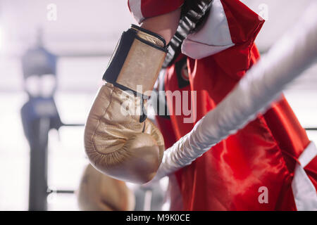 side view shot of sportswoman in red sportswear hanging her yellow boxing gloves on rope of ring. lost fight. tied fighter - Stock Photo