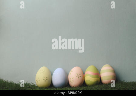A row of decorated eggs in different colours on artificial grass against blue grey background for Easter. Filtered to give muted, retro style. - Stock Photo