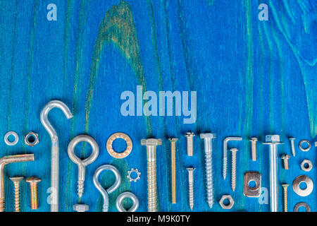 A lot of bolts nuts and washers of different types and sizes on a wooden background painted blue. - Stock Photo