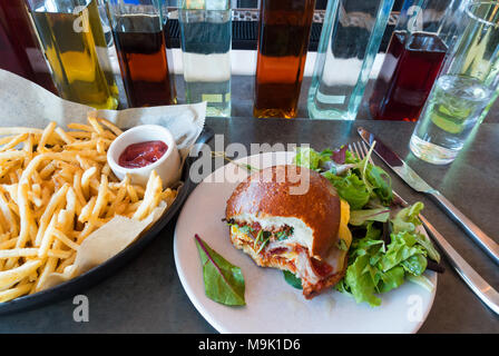 Egg and bacon sandwich on a soft toasted roll with mixed salad greens - Stock Photo
