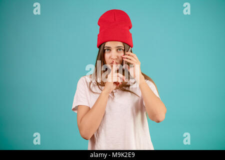 pretty stylish woman with mobile telephone on her ear is standing with the gesture of silence. keep secrets - Stock Photo
