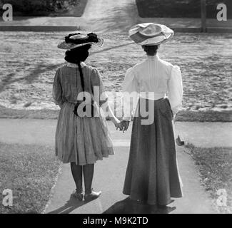 Two Victorian women face away and hold hands, ca. 1900. - Stock Photo