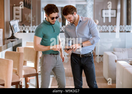 two active men are discussing new interior of the room. one ambitious man holding mobile phone and showing his ideas to his friend. order furniture. s - Stock Photo