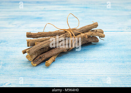 bundle of licorice roots Glycyrrhiza glabra on rustic table - Stock Photo