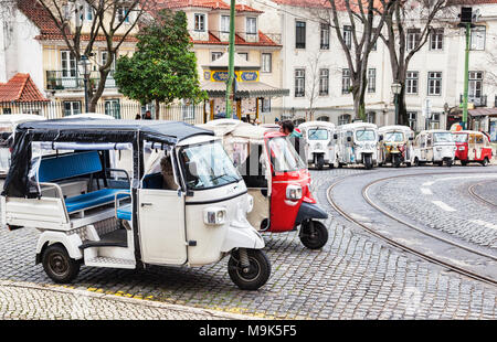 1 March 2018: Lisbon, Portugal - Covered tuk tuks ready for hire outside Lisbon Cathedral. - Stock Photo