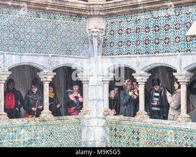 5 March 2018: Sintra, Portugal - Tourists with camera phones under a colonnade at Pena Palace, making the most of a very wet day. - Stock Photo