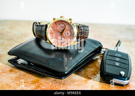 an expansive and stylish brand new set of a black shining leather wallet and a watch with a remote car key kept on a marble floor - Stock Photo