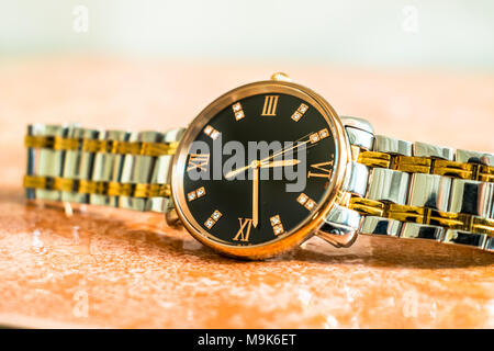 an expensive and stylish brand new silver and golden man's thin dial watch kept on a marble floor - Stock Photo