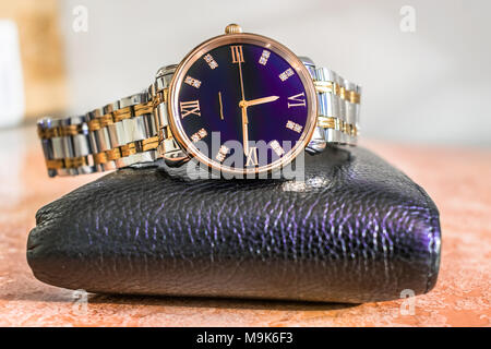 an expansive and stylish brand new set of a black shining leather wallet and a silver and golden man's thin dial watch kept on a marble brownish floor - Stock Photo